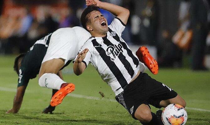 Hugo Martínez del Libertad cae de forma aparatosa ante el balón. Cuotas y picks del Libertad vs Universidad Católica.