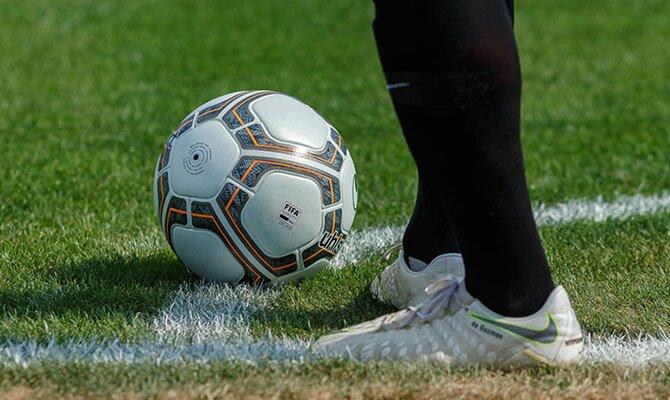 Los pies de un jugador a punto de golpear el balón para sacar un córner. Cuotas del Sevilla vs Atlético de Madrid.