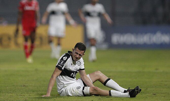 Luis Cáceres del Olimpia se duele en el suelo de un golpe. Cuotas Olimpia vs Deportivo Táchira.