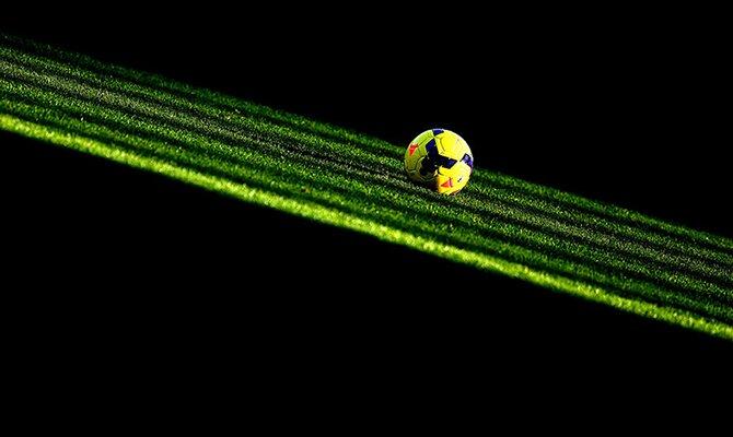 Balón amarillo iluminado sobre el césped en la oscuridad. Cuotas para el Olimpia vs Internacional.