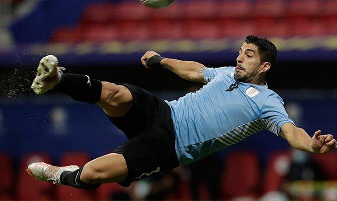 Luis Suarez tratando de ejecutar una volea en el aire. Cuotas y picks Uruguay vs Paraguay.