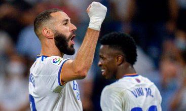 Karim Benzema celebrando con el puño en alto, con Vinícius de fondo. Apuestas Inter vs Real Madrid.